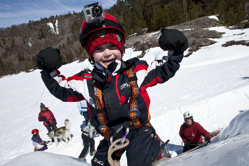 Little boy smiling after climbing up a small slope.