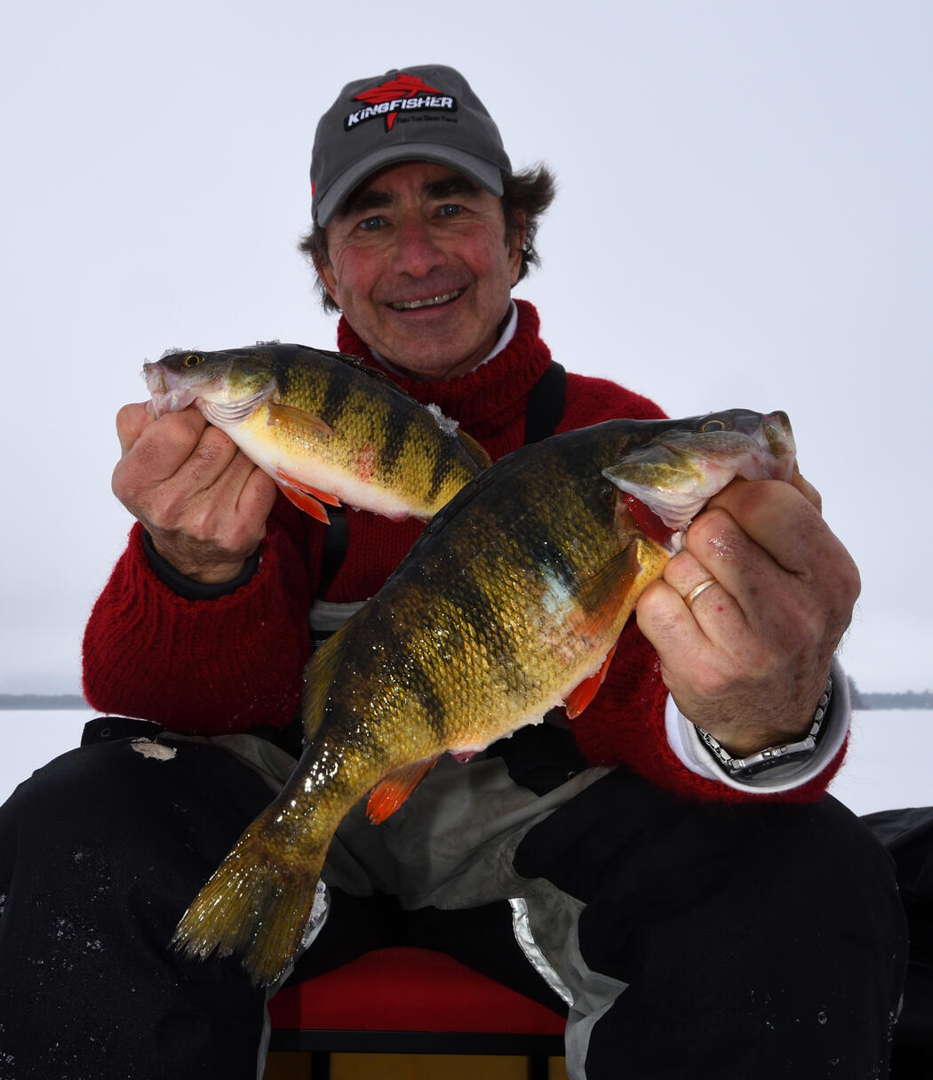 ice angler holding perch