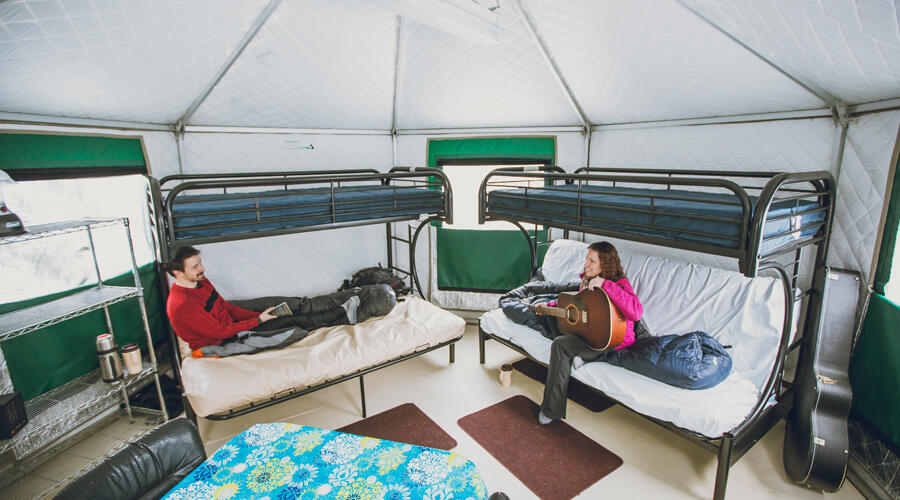 A couple sitting on bunk beds inside a yurt.