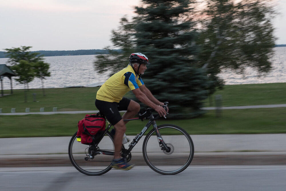 Man cycling on road next to water