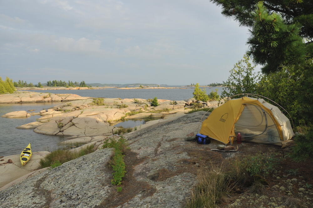 Tent pitched on rocks next to water