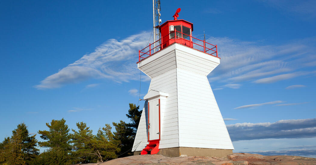 white lighthouse with red top perched on rock on Georgian Bay
