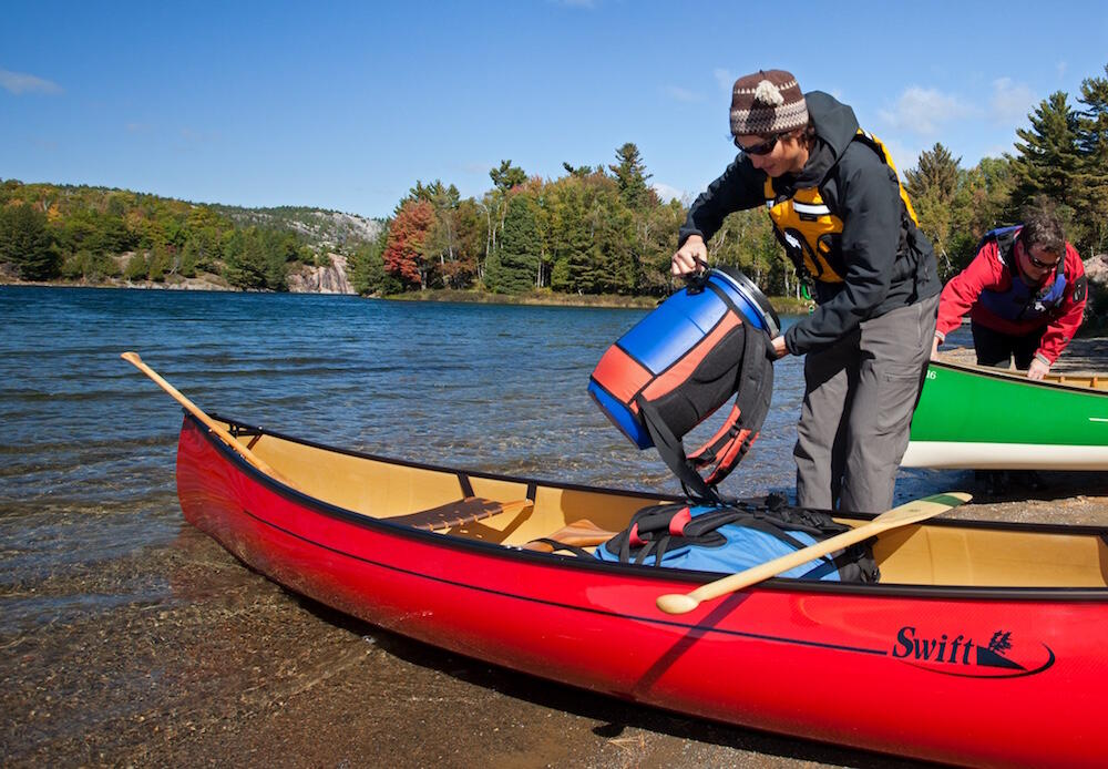 Woman putting a barrel pack into a red canoe at lake shore.