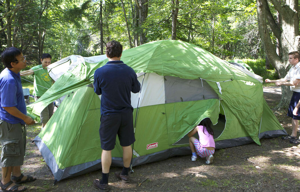 Group of people setting up a tent with Ontario Parks staff.