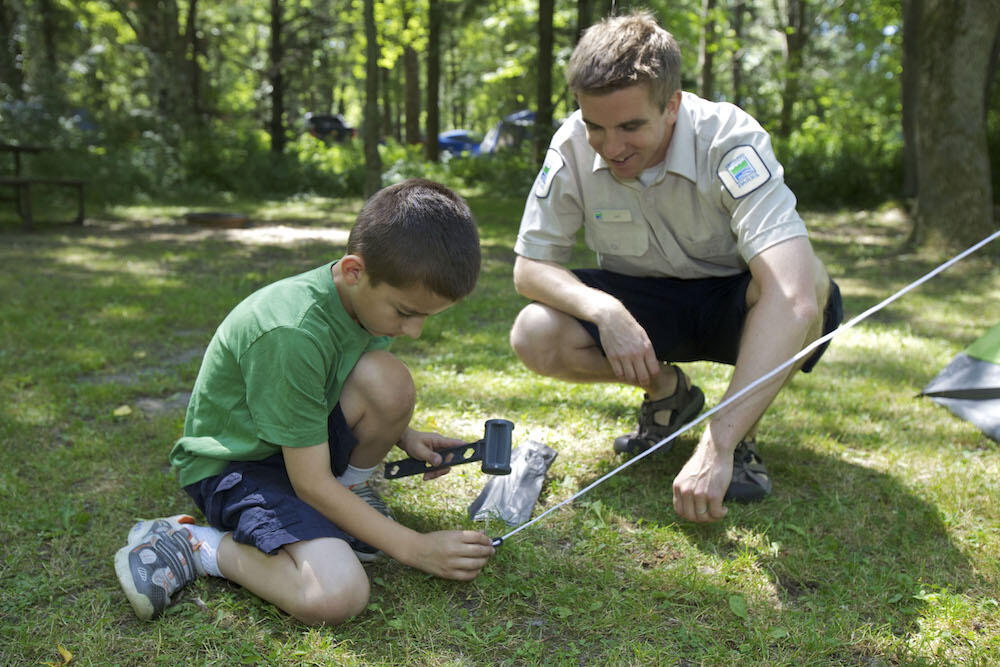 Ontario Parks staff helping a child with a tent peg.
