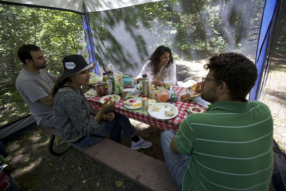 Group of people sitting at a picnic table with screened tent over it.