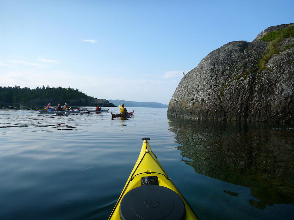 View from kayak of other kayakers on waters of Lake Superior