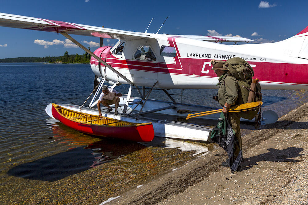 Float plane parked on beach with a red canoe beside it.