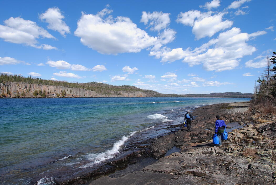 Two people walking with dry bags along rock coast of Lake Superior
