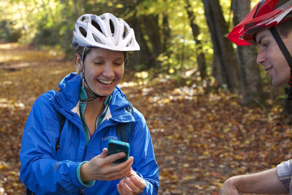 Woman in cycling helmet holding a cell phone