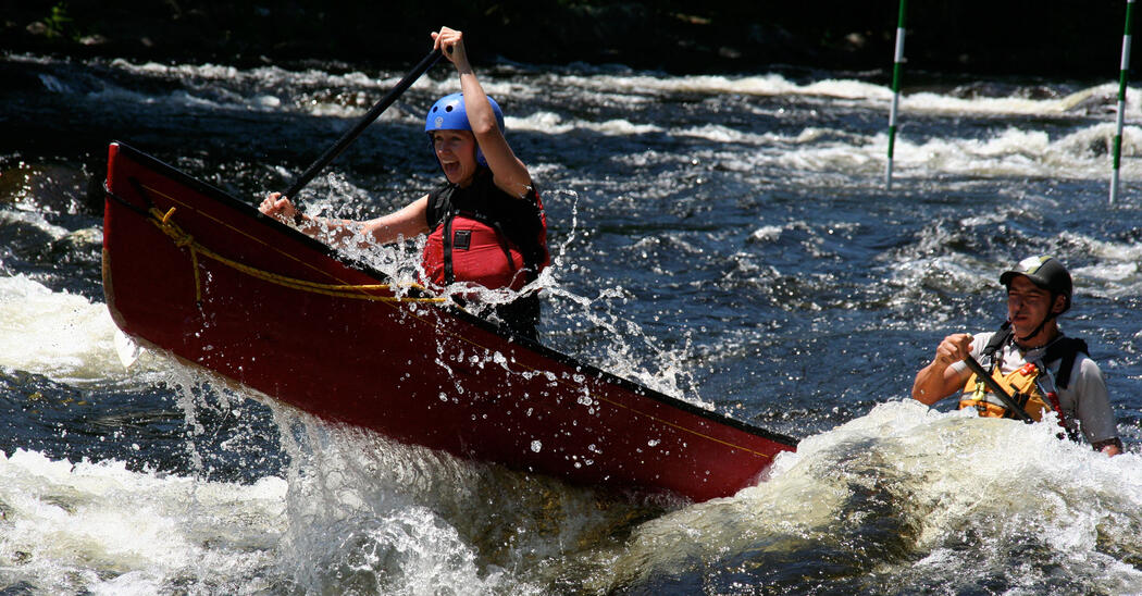 A red canoe with two people paddling in whitewater rapids.