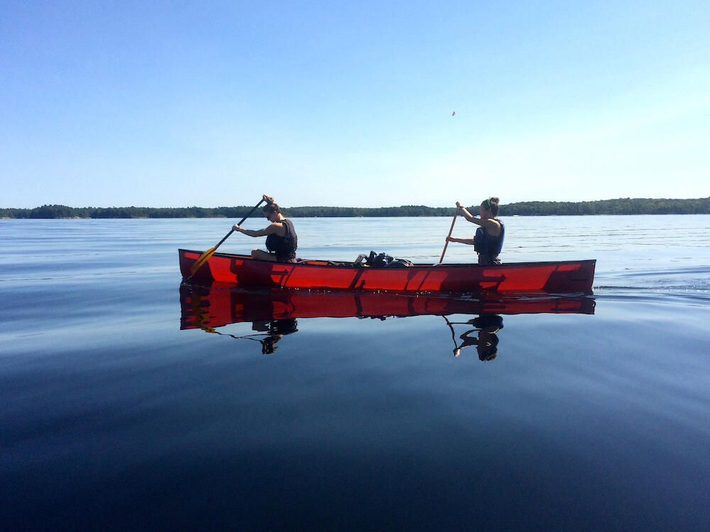 Two people paddling red canoe on a lake