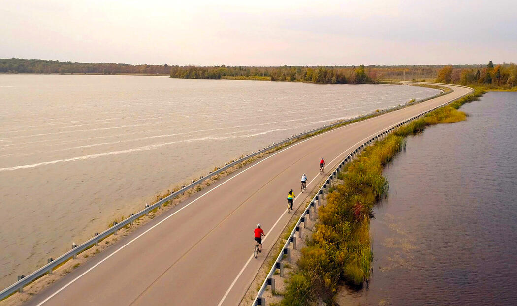 Group of cyclists riding on paved shoulder over causeway.