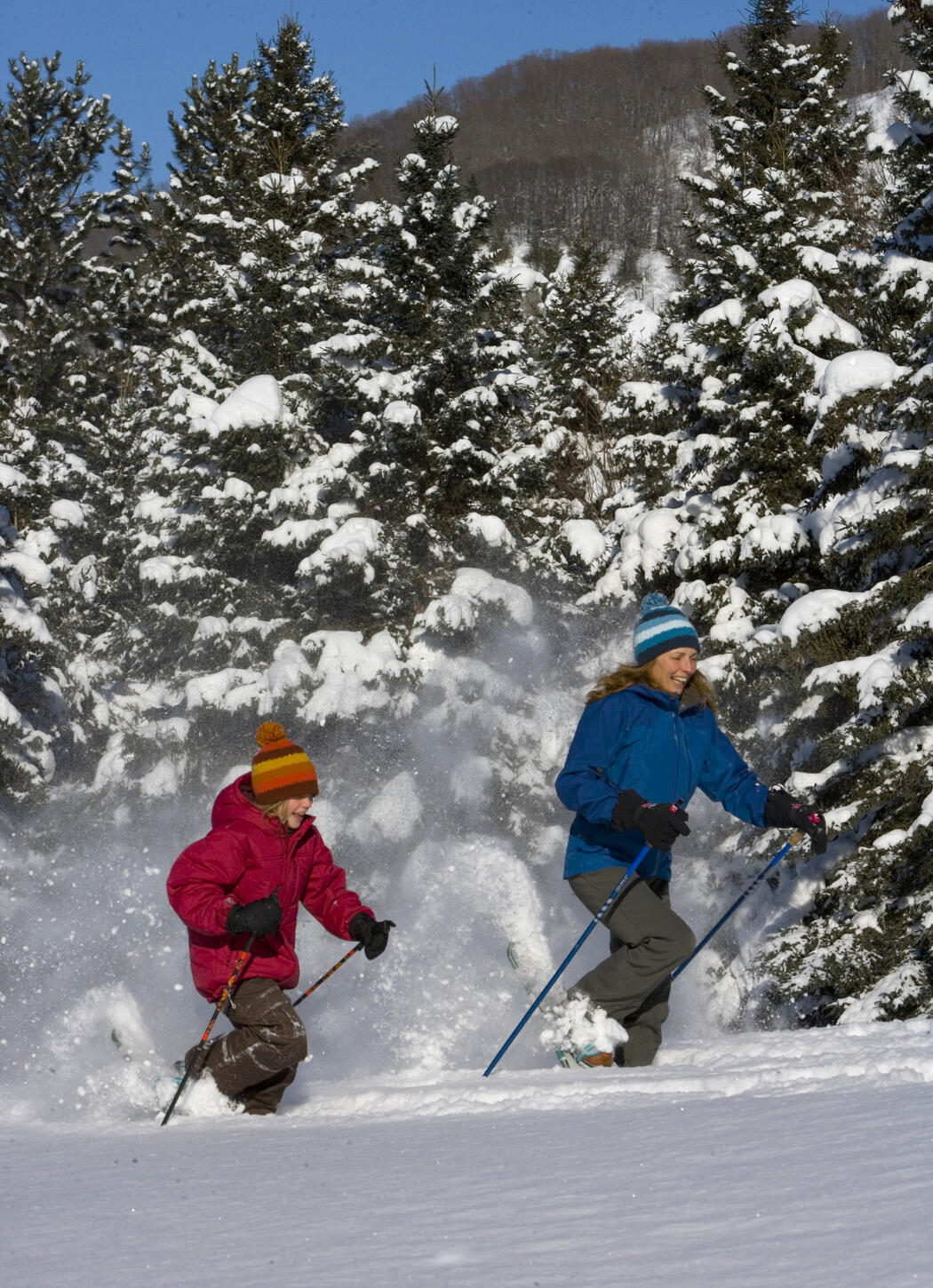 Woman and girl running on snowshoes in deep powder snow