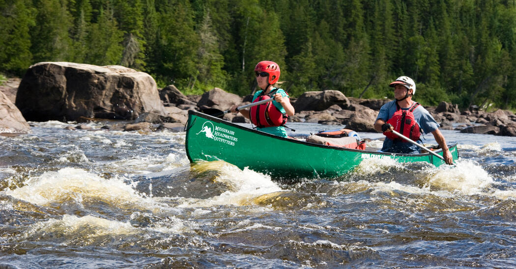 Two people paddling in green canoe in whitewater rapids
