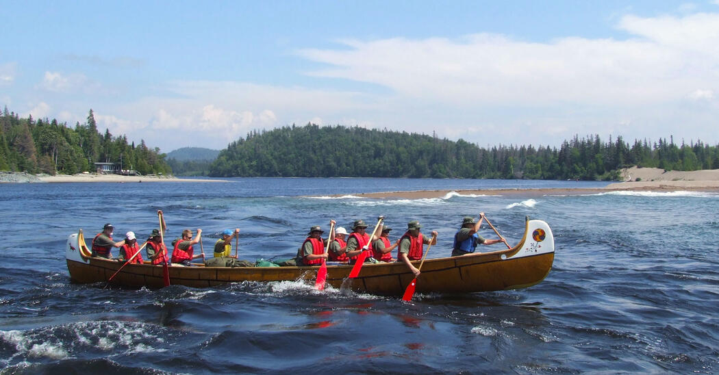 Eleven people paddling a replica voyageur canoe on Lake Superior