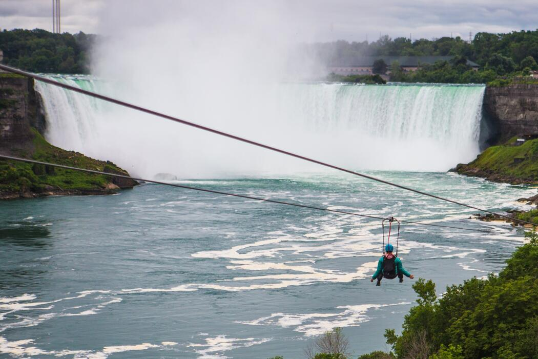 Person in a harness hanging from a zipline in front of Niagara Falls.