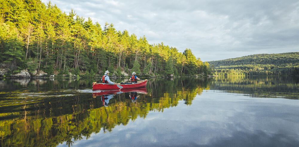 two people paddling a red canoe on a calm lake