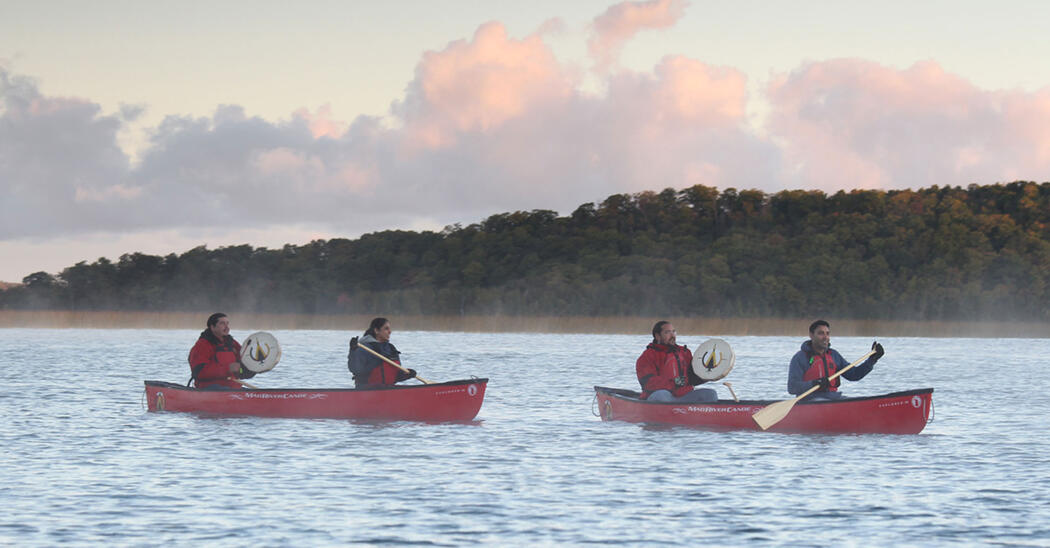 two red canoes on lake surrounded by light mist, Indigenous guides with drums in stern