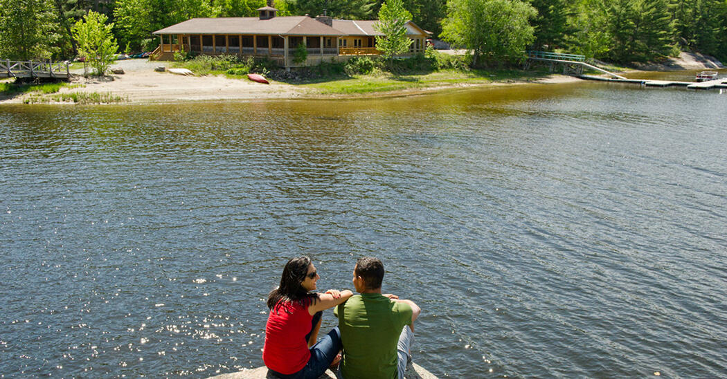 Man and woman sitting on rock looking at lodge on other side of river
