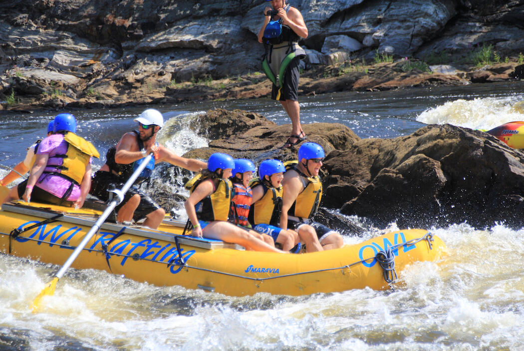 Family in a raft with guide steering in white water.