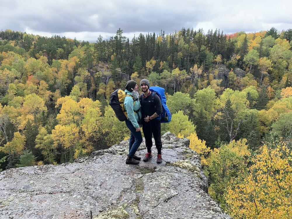 Man and woman with backpacks on standing on lookout over forest