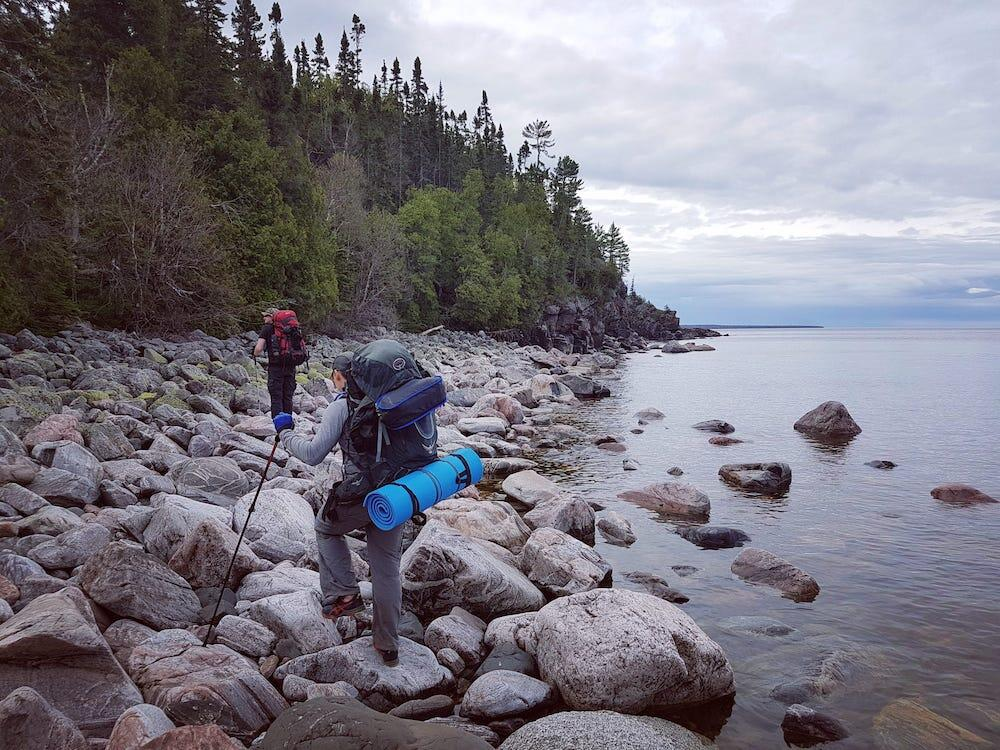 Two people backpacking on rocks at water's edge
