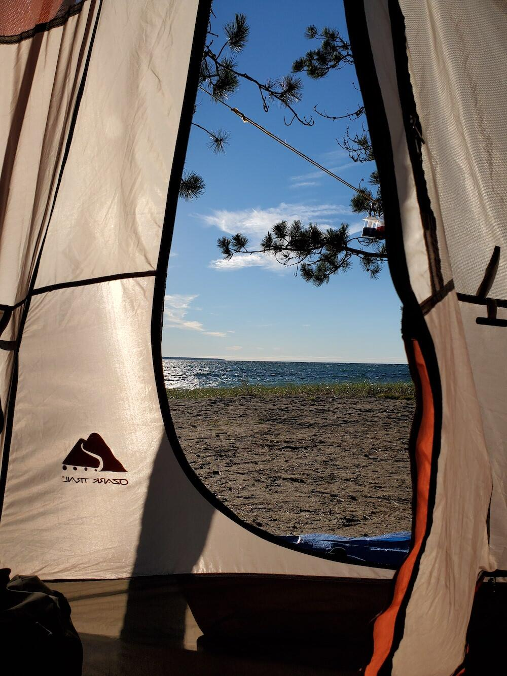View from inside tent of beach and lake