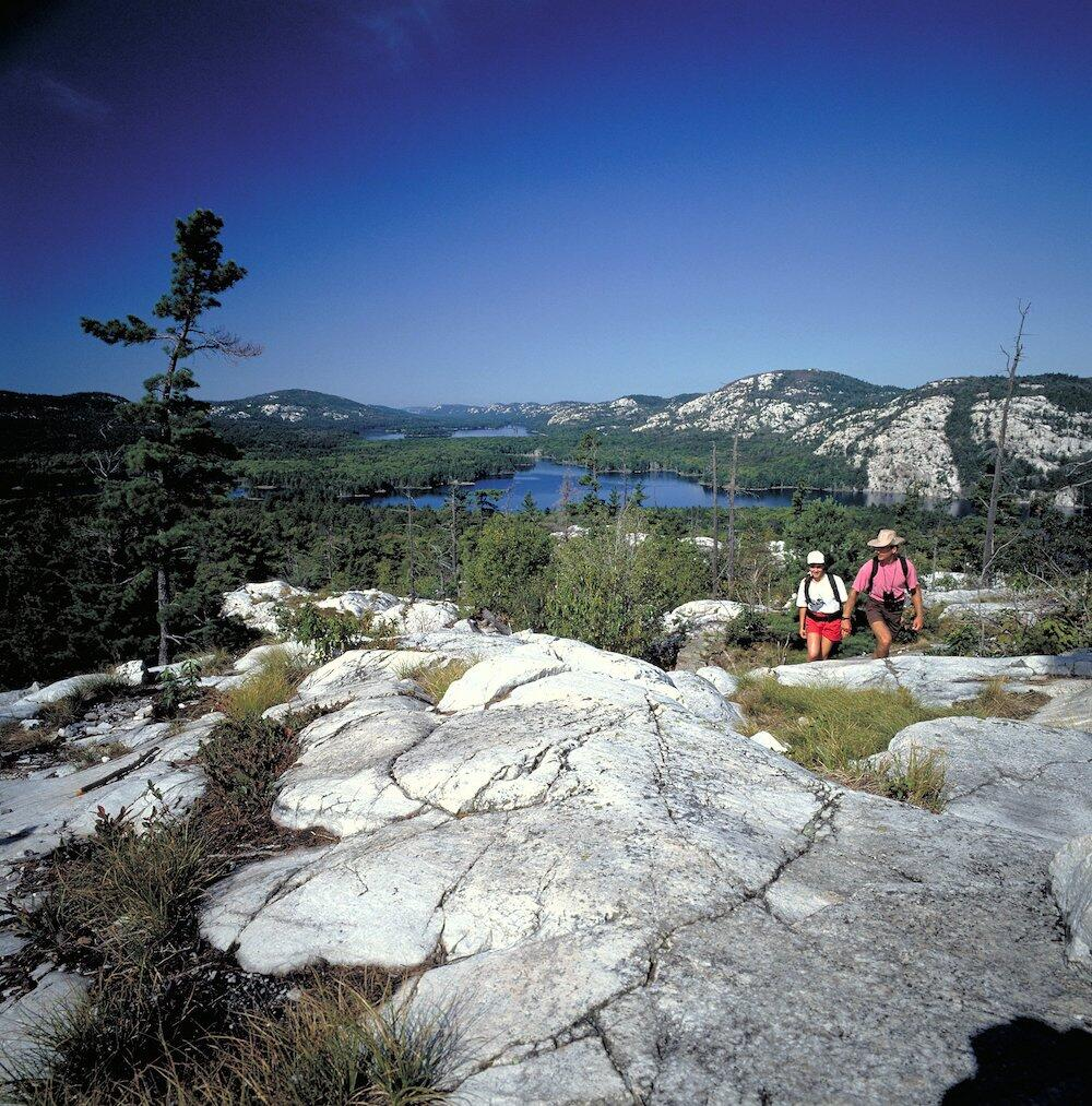 Two people coming to the top of The Crack with lake in the distance