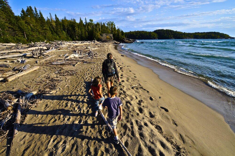 Family walking on the sand next to the lake with driftwood.