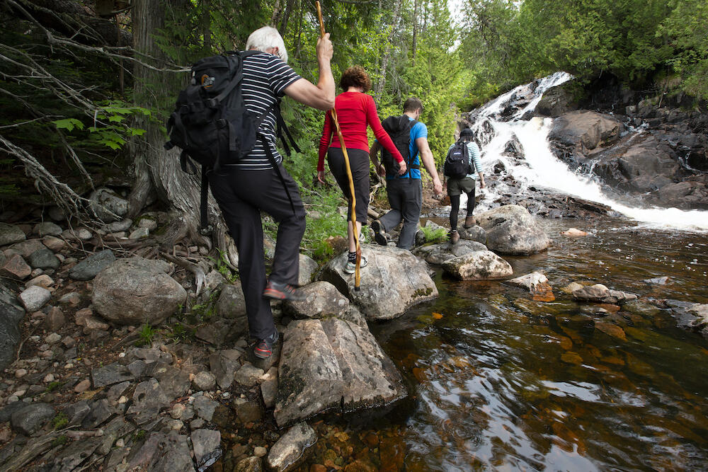 Four people hiking on rocks along stream leading up to waterfall.