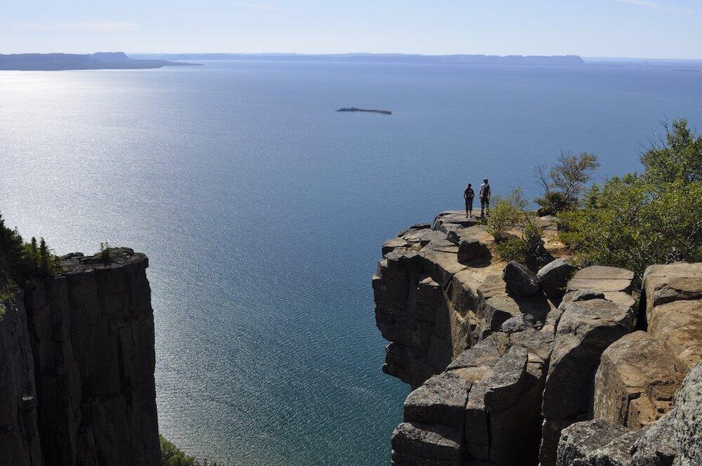 Two people standing on cliff overlooking Lake Superior