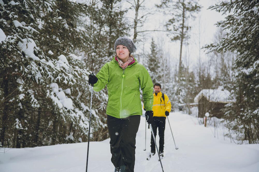Man and woman on cross country skis going through the forest