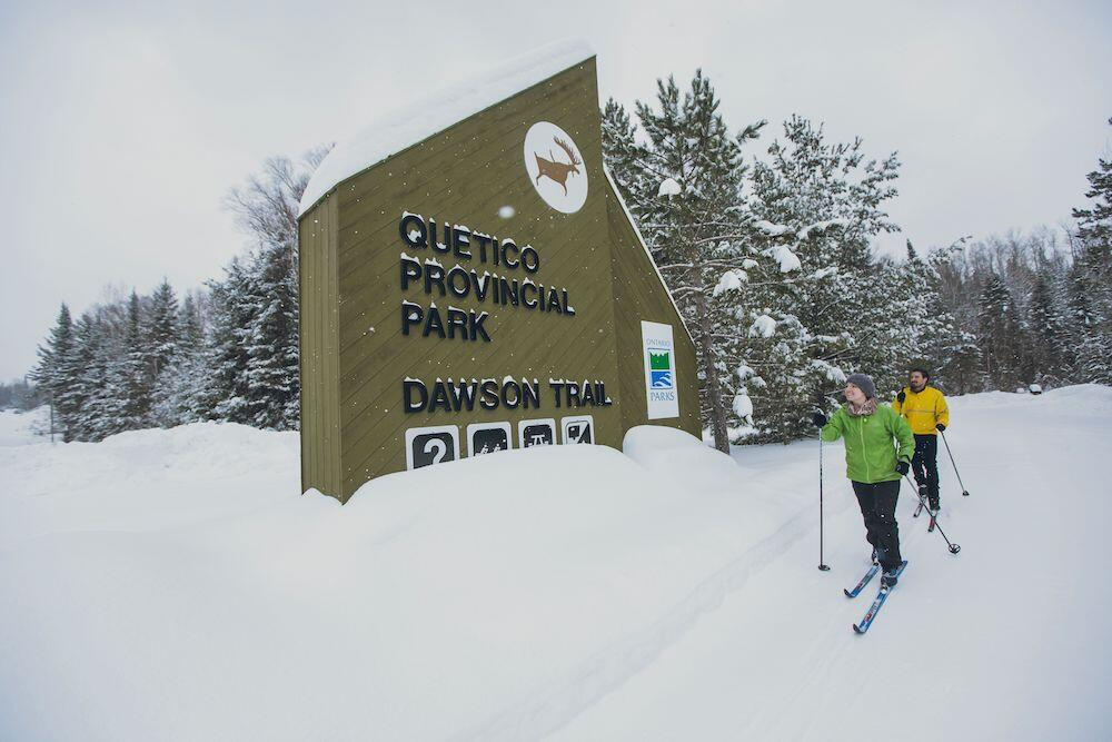 Two people cross country skiing in front of Quetico Provincial Park sign