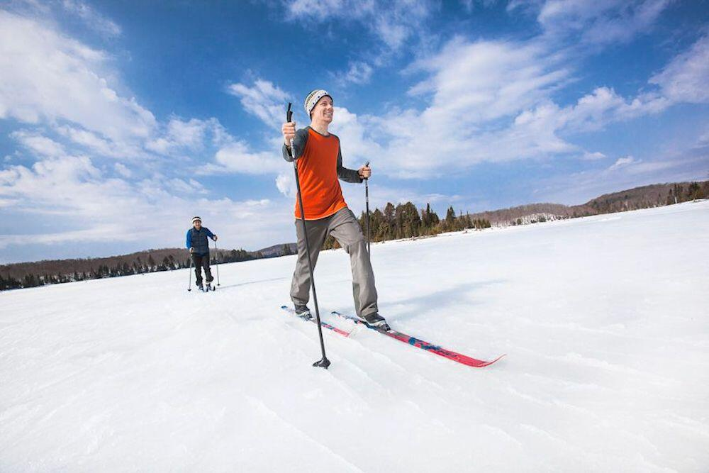Two people cross country skiing across a frozen, snow-covered lake