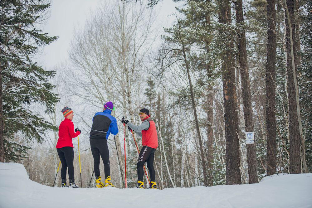 A group of three people stopped on a cross country ski trail