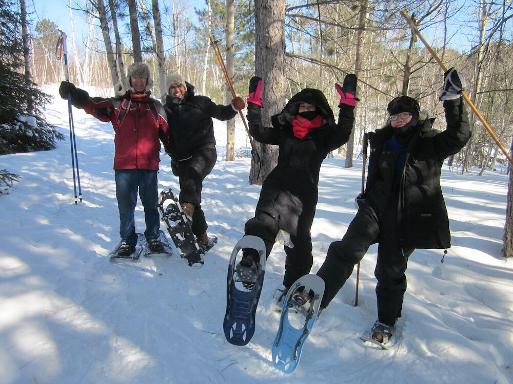 Four people wearing snowshoes on a trail