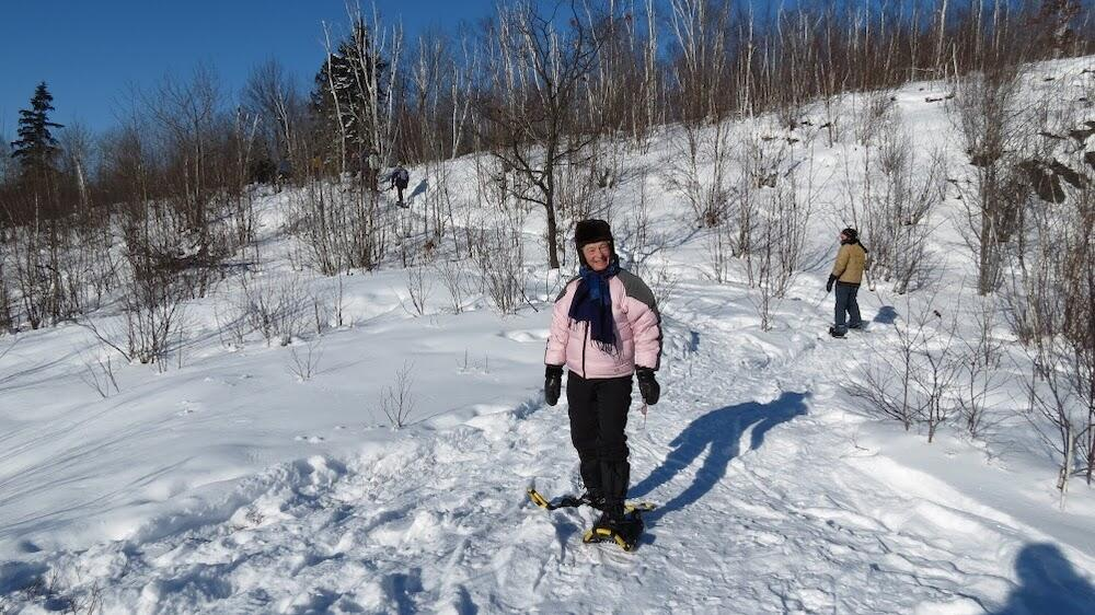 Woman on snowshoes with man in background.