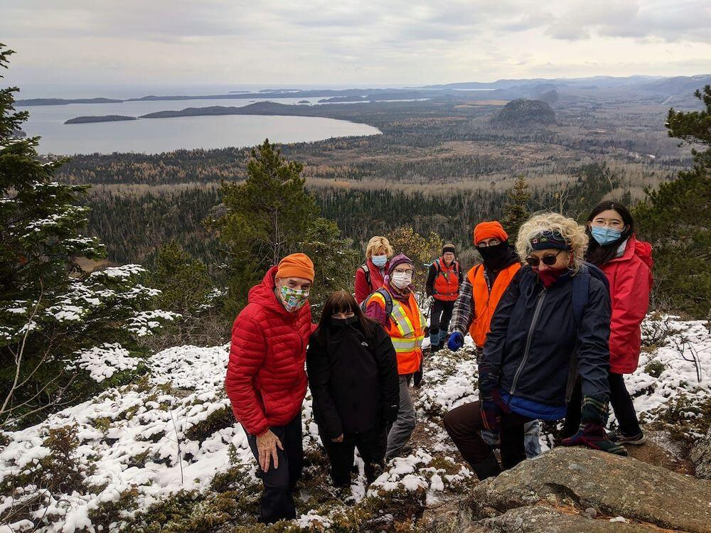Group of people wearing masks at top of lookout over lake in the winter