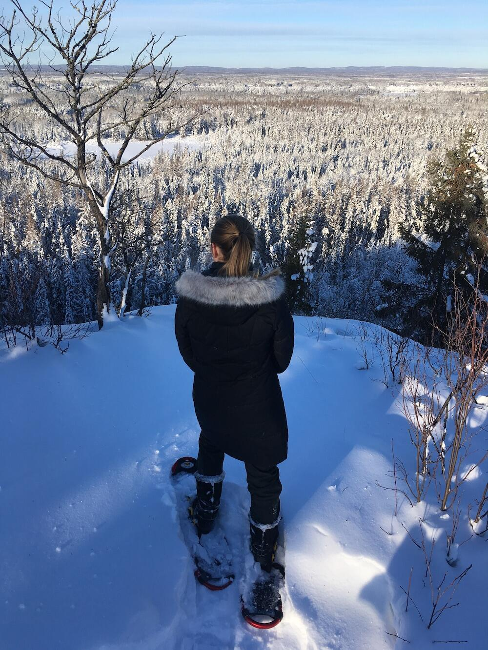Woman on snowshoes at top of snowy lookout