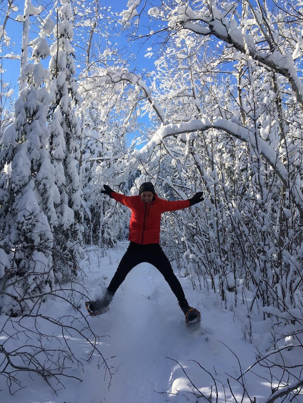Woman on snowshoes jumping on a snowy trail