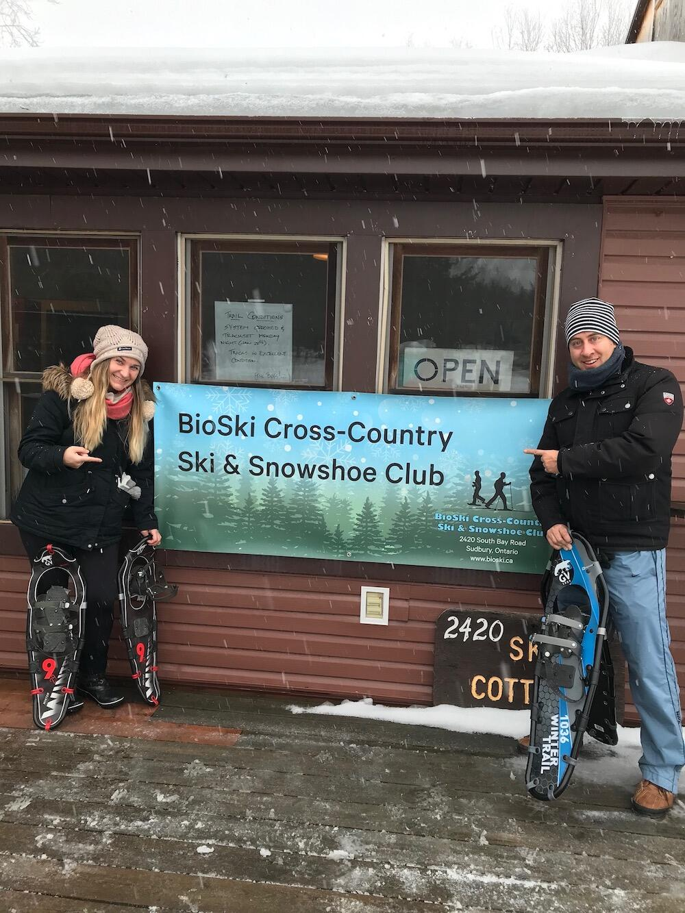 Man and woman standing with snowshoes on either side of BioSki sign
