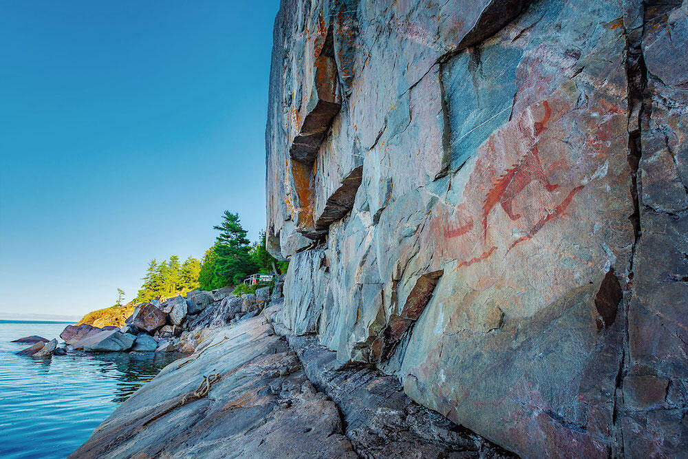 Pictographs on cliff face next to water.