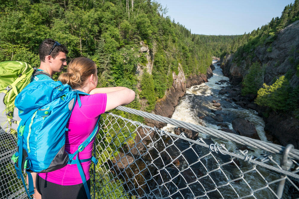 Two backpackers stand on suspension bridge