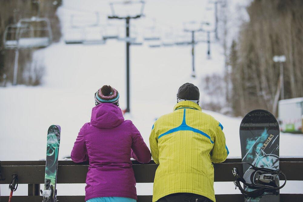 A skier and snowboarder standing at the bottom of the hill looking up at the lift