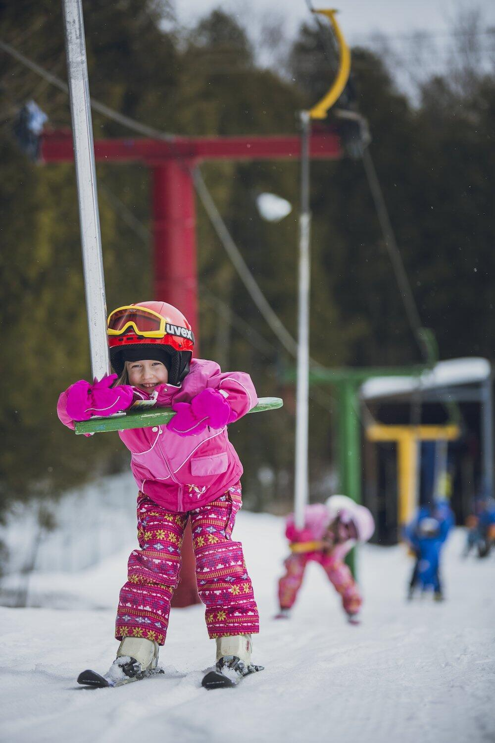 A little girl on skis riding a T-bar.
