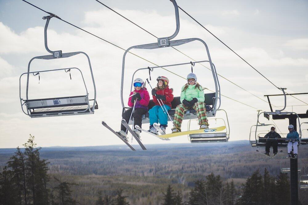Three girls, two on skis and one on a snowboard, on a chairlift.