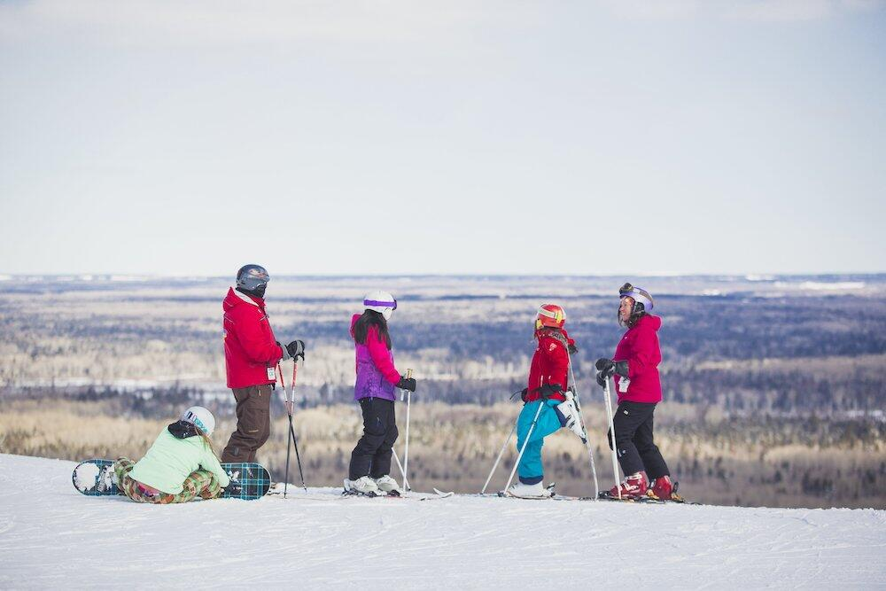 Two adults and three kids at the top of the ski hill