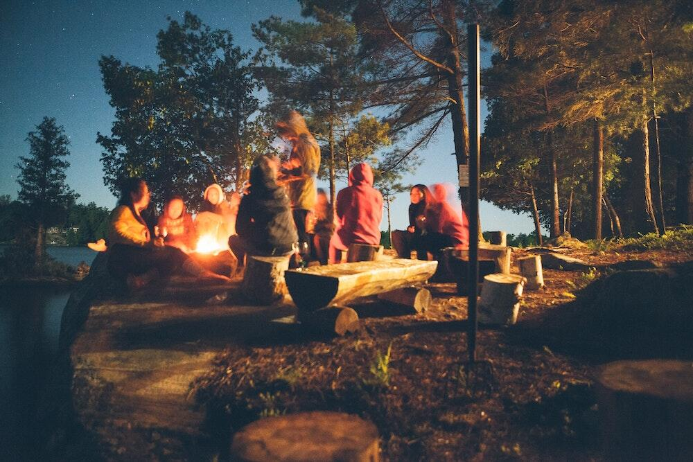 People sitting next to fire at night