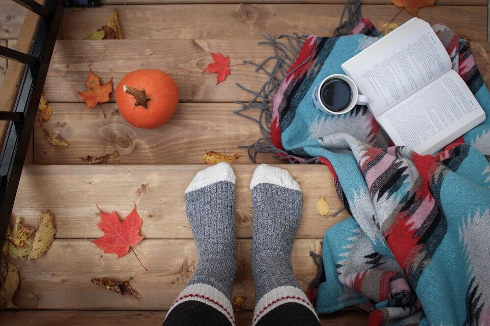 Looking down at sock feet on wooden stairs with coffee, blanket, book and pumpkin.